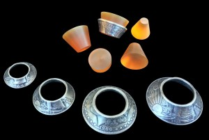 A folded-over Morgan Silver Dollar and 4 other coins folded over using these new and improved folding cones.
